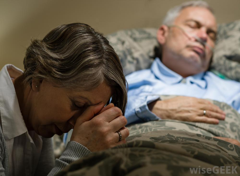 woman-praying-near-bedside-of-sick-man